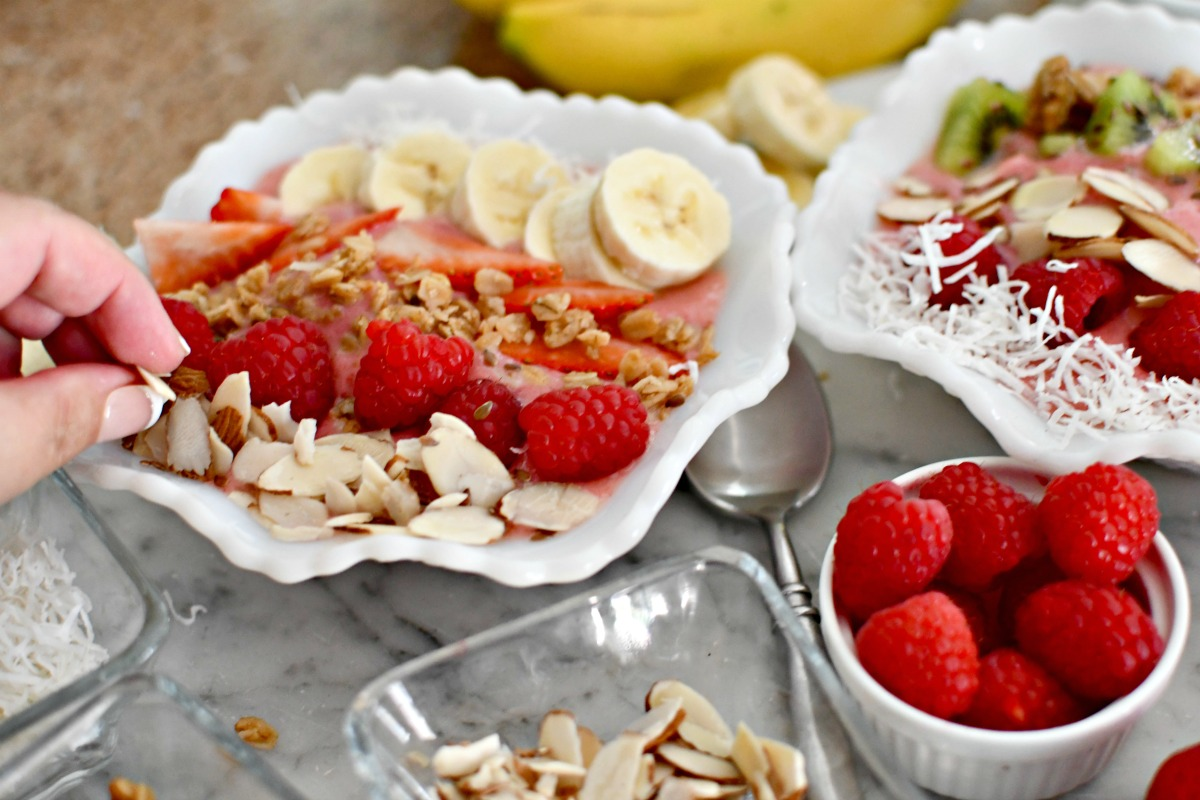 sprinkling toppings on smoothie bowls
