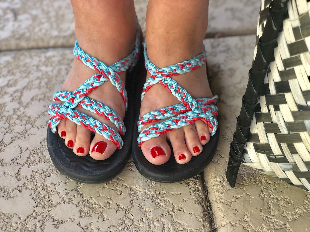 feet in strappy sandals with painted red toenails