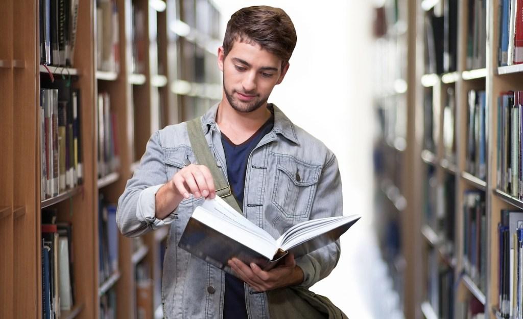 man at library reading book