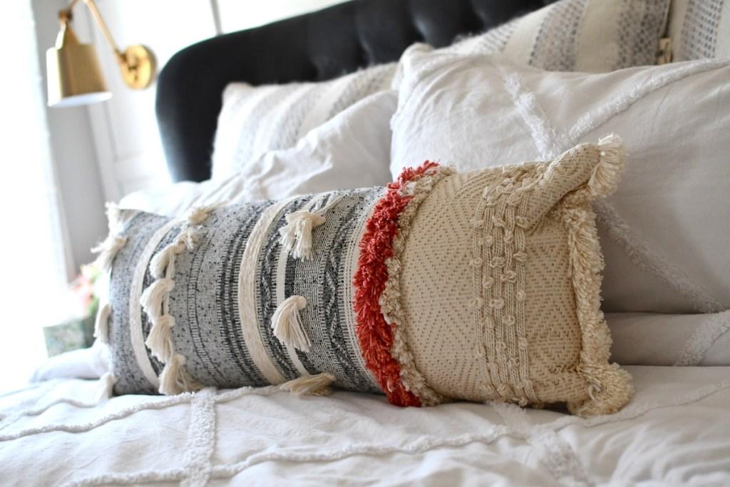 lumbar tassel pillow on white bed