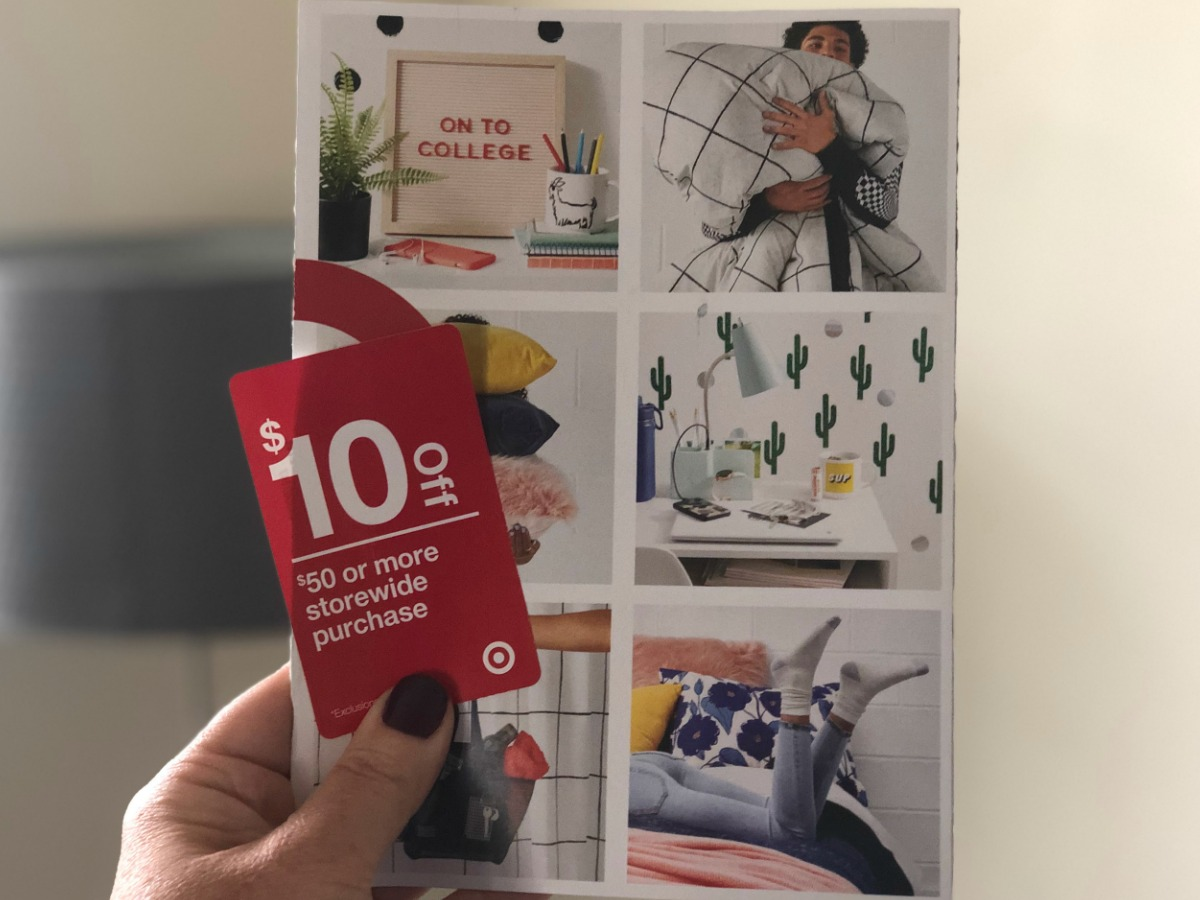 hand holding red coupon in front of mail