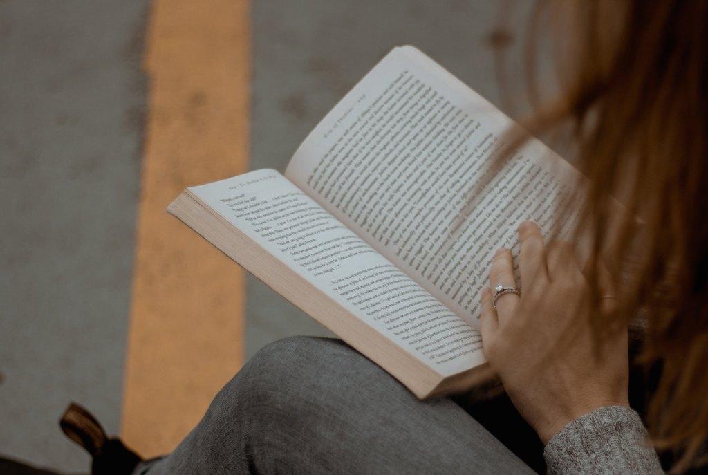 women reading open textbook