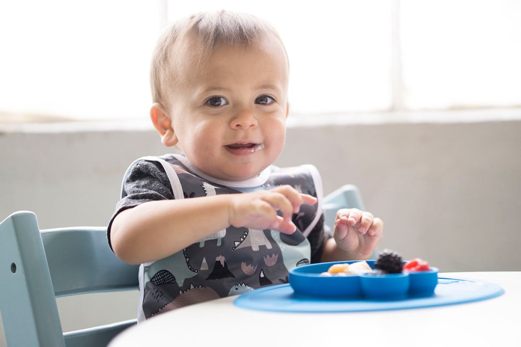 toddler eating from sesame street ezpz mat