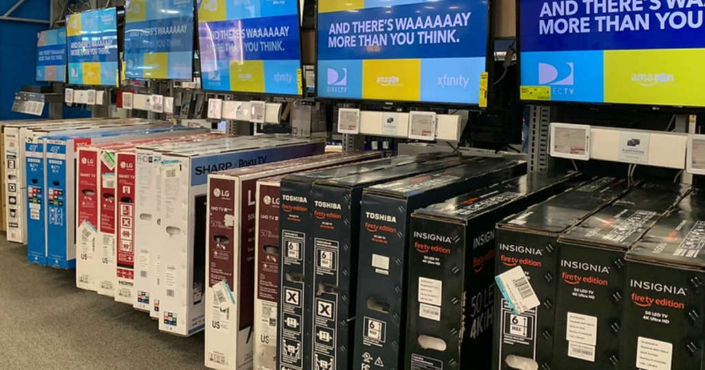 tv boxes lined up below television displays in store