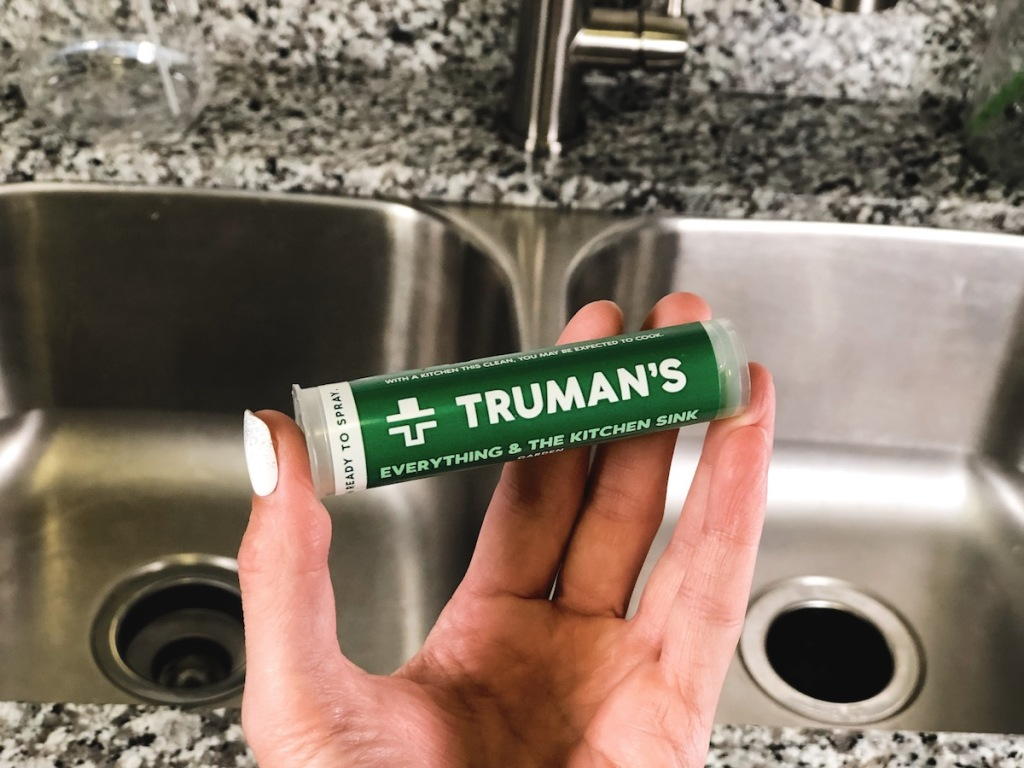 woman hand holding trumans kitchen cleaner in stainless steel kitchen sink