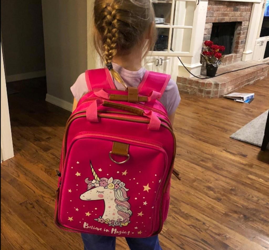 girl wearing hot pink unicorn bookbag