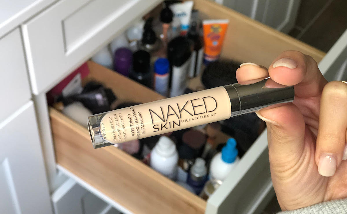 hand holding urban decay concealer
