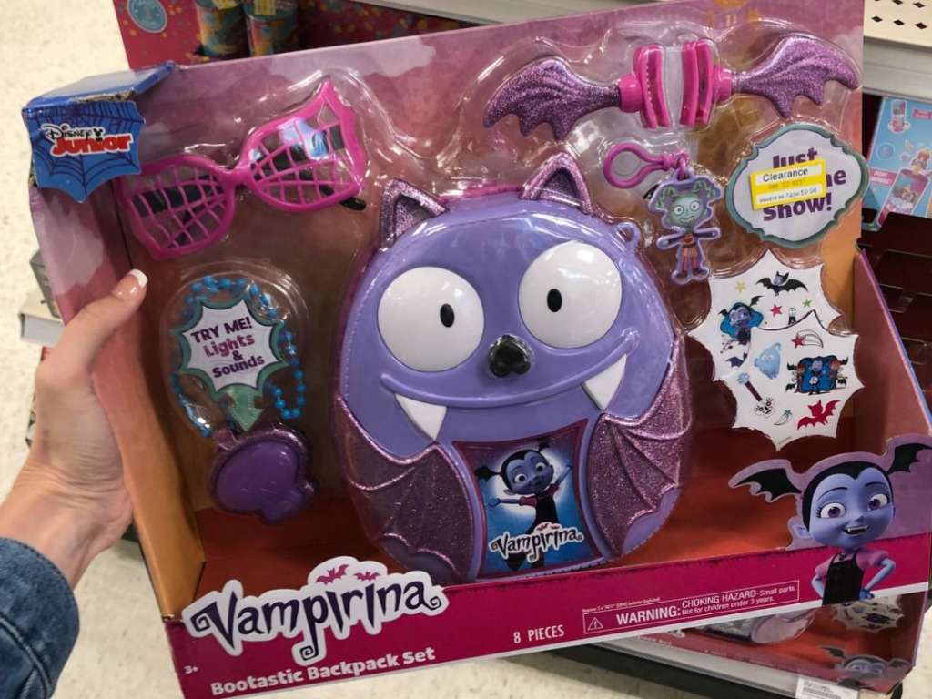 hand holding purple vampire toy in package at store