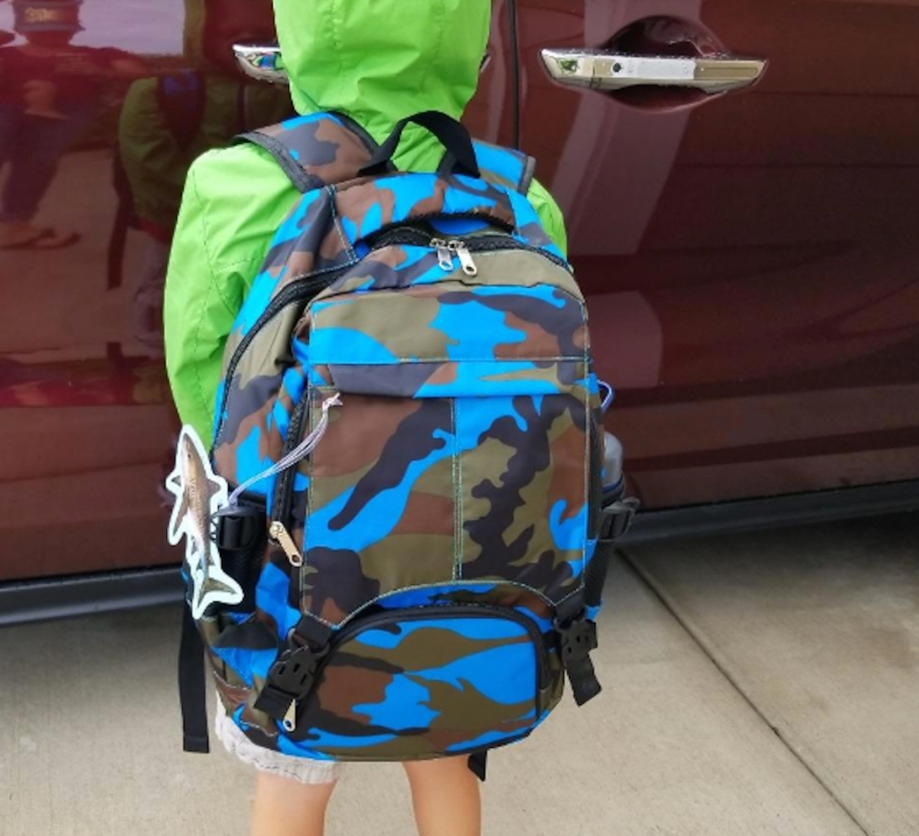 kid wearing green raincoat and blue camo backpack