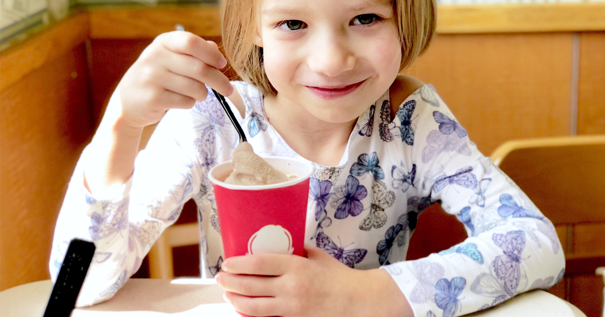 girl eating a Frosty at a Wendy's restaurant