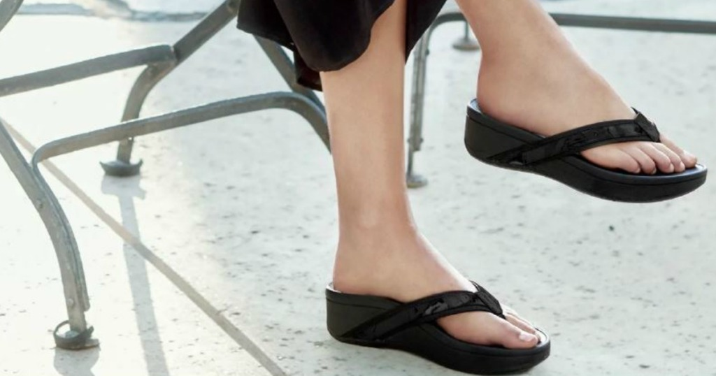 woman's legs sitting in chair wearing flip flops