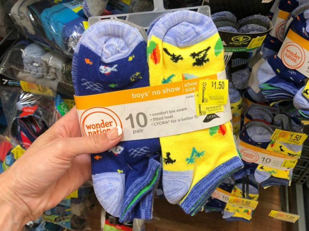 hand holding colorful pairs of boys socks in store