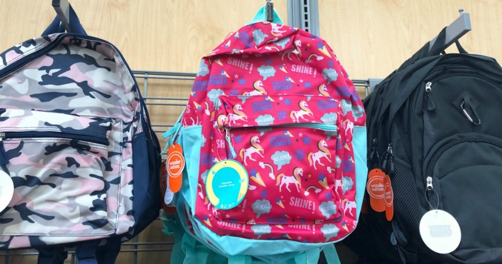 store display with three backpacks hanging