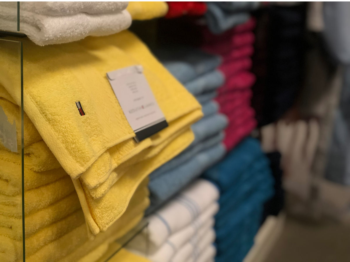 yellow tommy hilfiger towels folded on display in store
