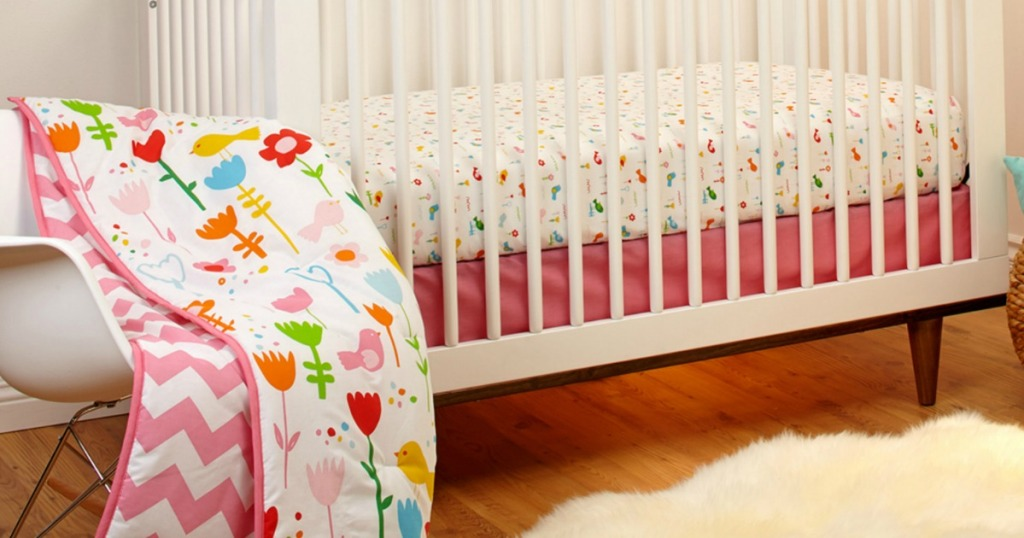 flowery crib blanket set with white nursery furniture