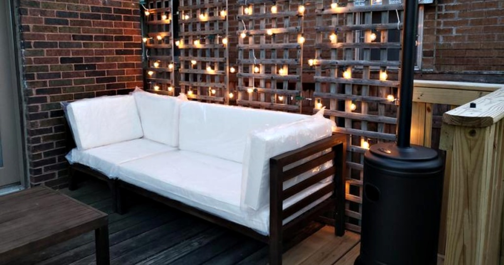 part of acacia wood sectional sofa on patio with lights