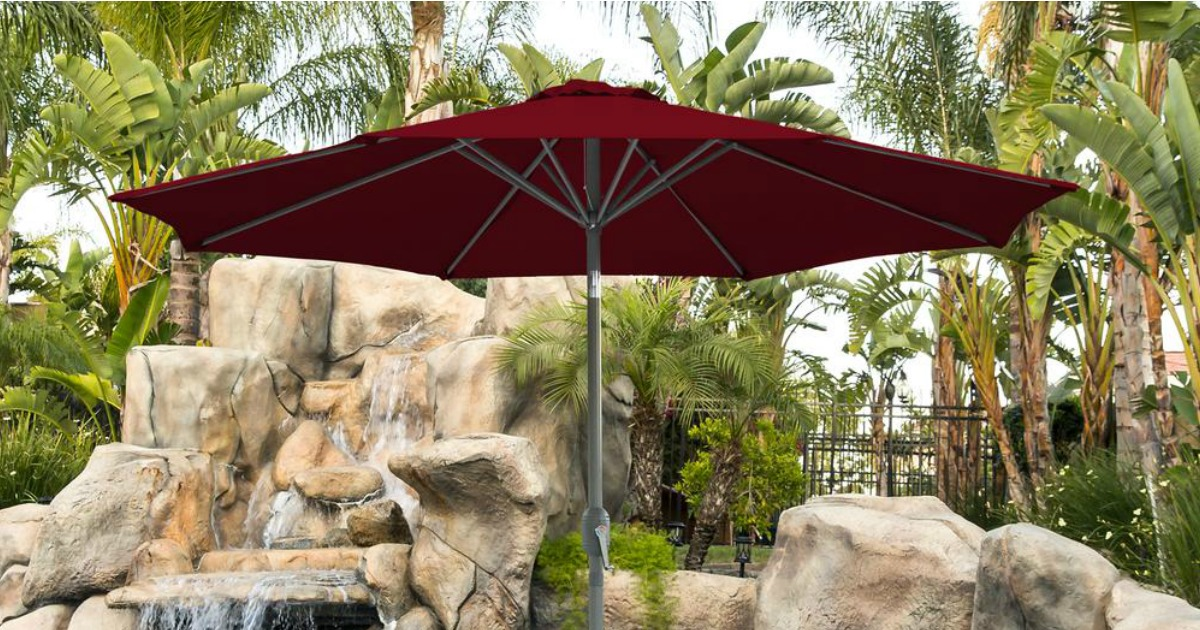 red patio umbrella outside in front of a water & rock feature