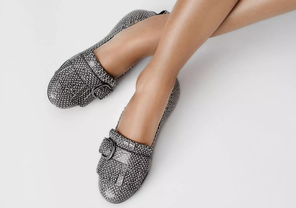 woman wearing snake print loafers