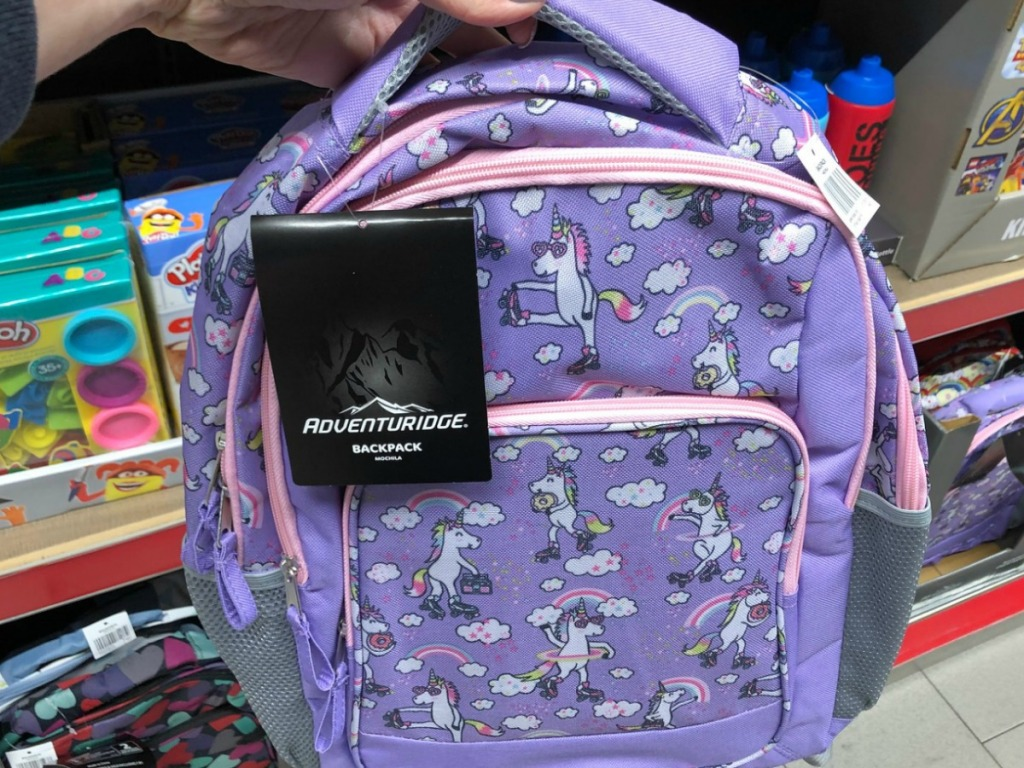 hand holding purple backpack with unicorns by store display