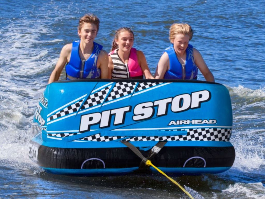 3 people on Airhead Pit Stop 3-Person Towable Tube on the water