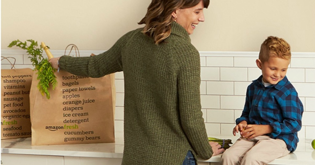 Woman in kitchen with Amazon Fresh grocery bags