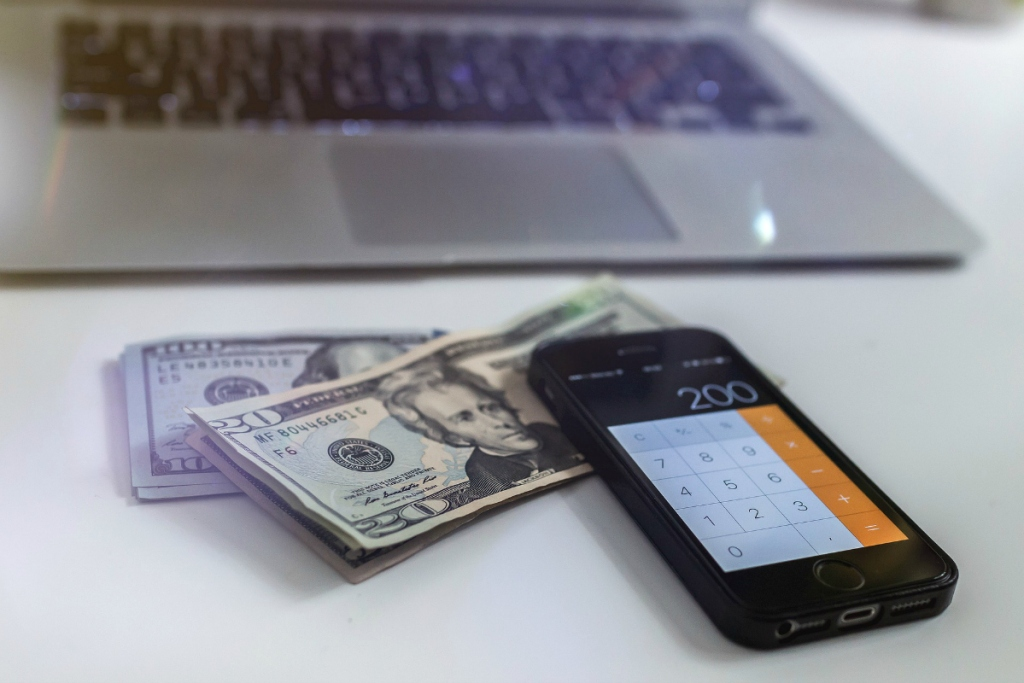 stack of cash with iphone and laptop