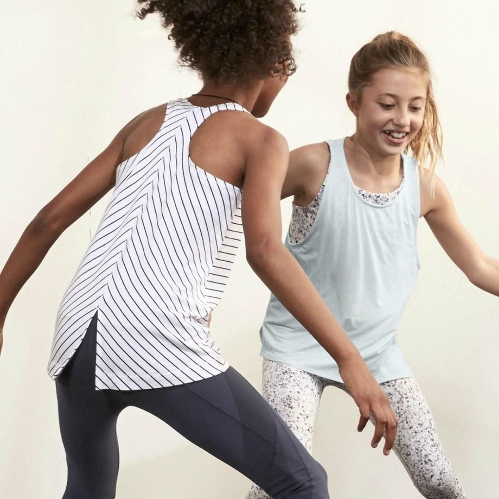 Girls wearing Athleta girls tank tops and playing basketball