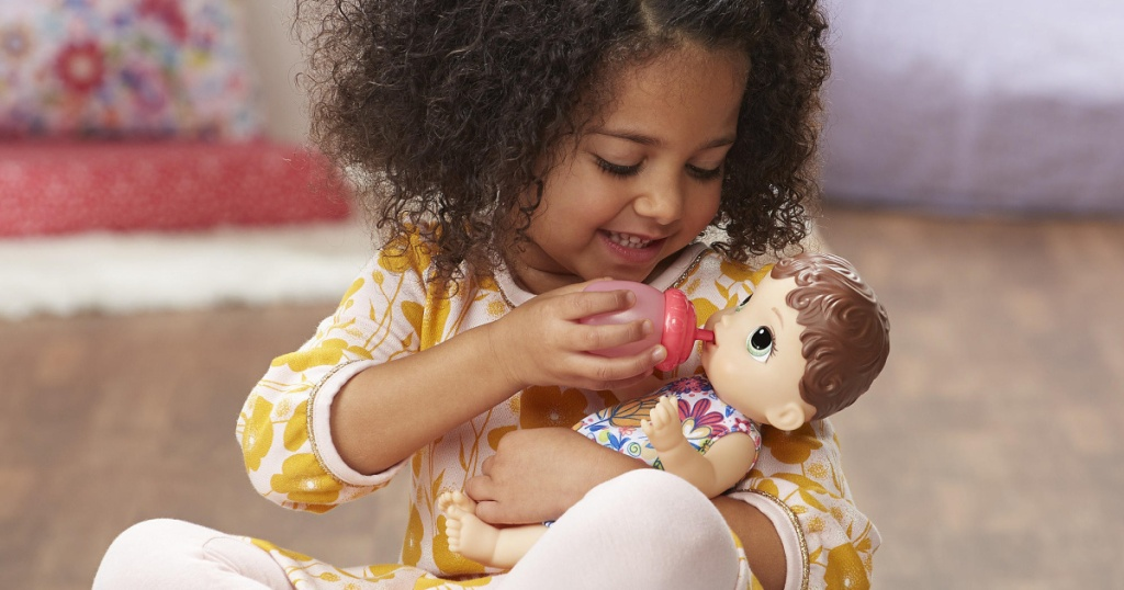 girl holding baby alive doll