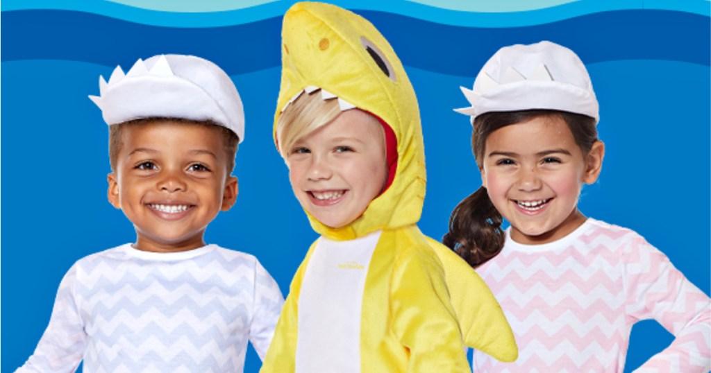 3 kids wearing baby shark costumes