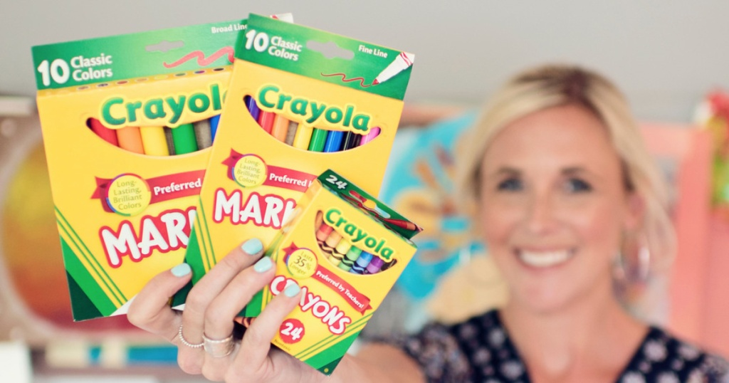 Woman holding crayola markers and crayons back to school