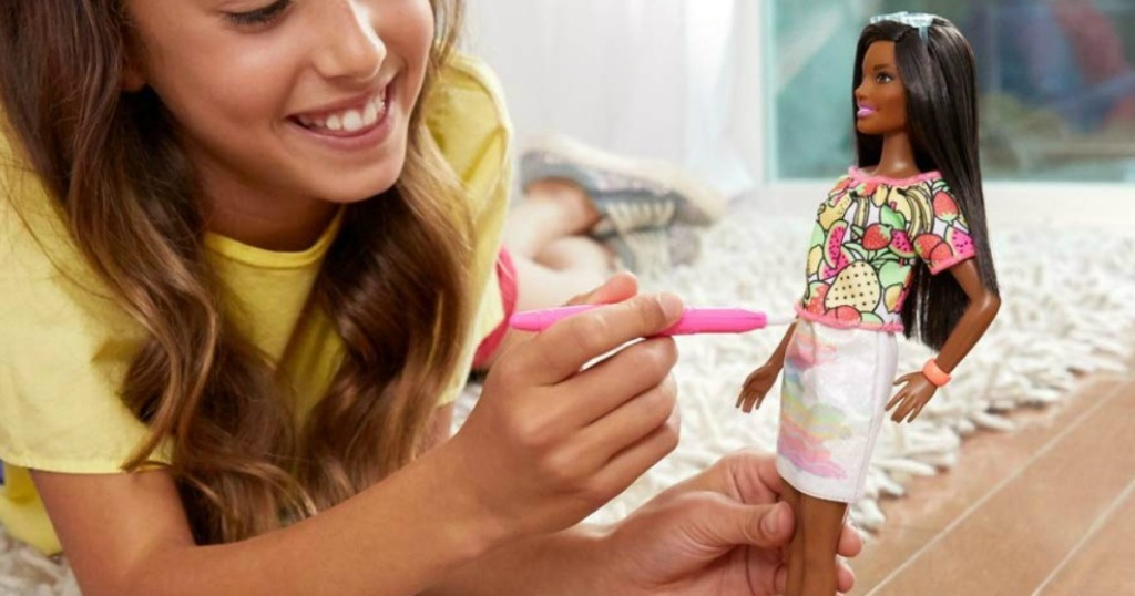 girl playing with Barbie doll