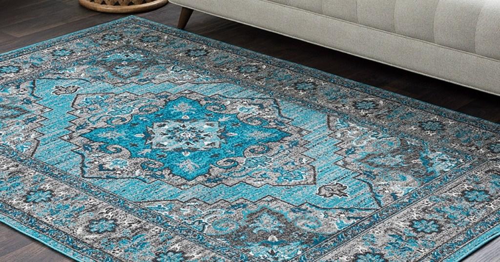 Blueish green rug on wood flooring