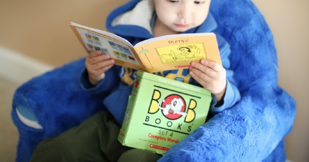Child reading BOB books set in blue shark chair