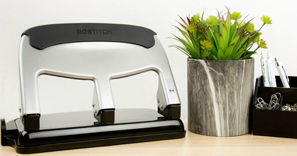 3-hole punch on desk with plant