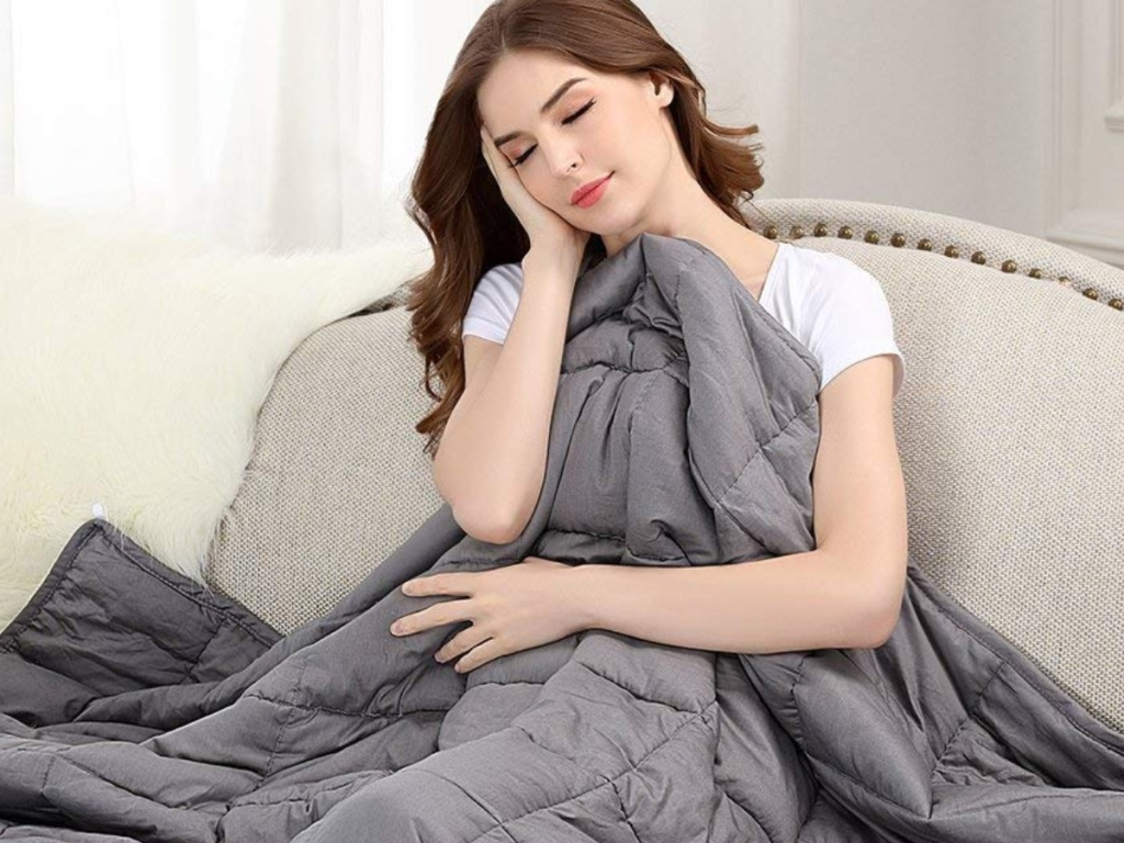 Woman sitting in a chair sleeping with Buzio Weighted Blanket