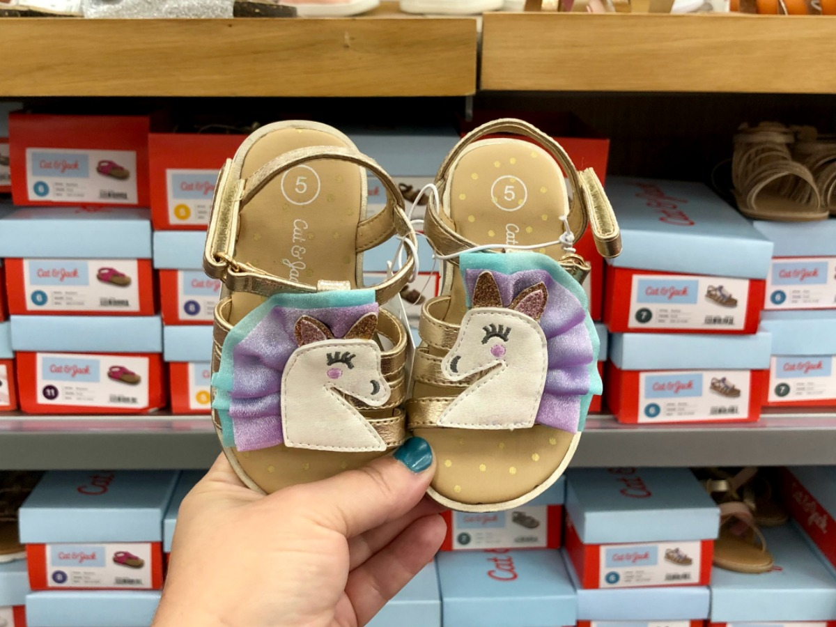 hand holding unicorn sandals in target