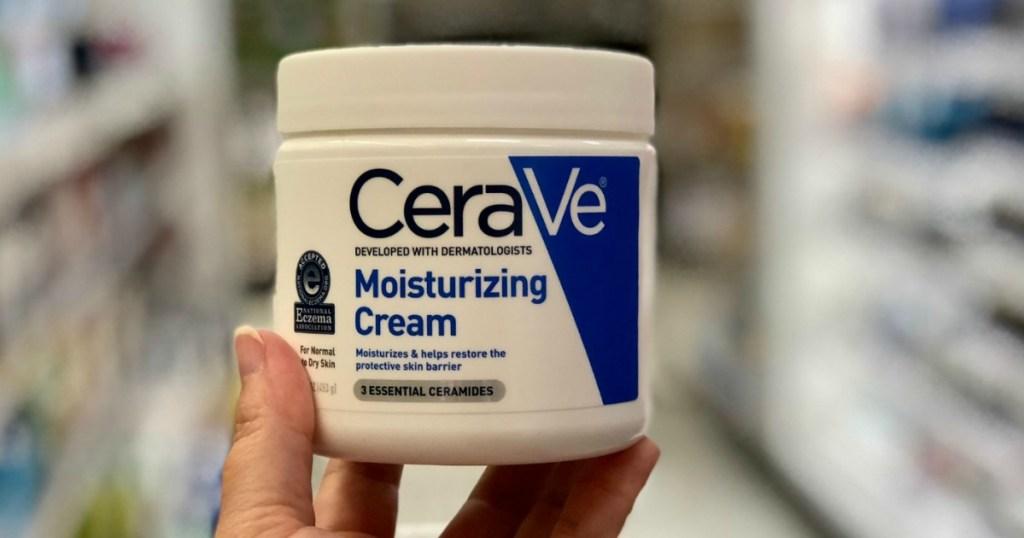 Jar of CeraVe Moisturizing Cream in hand in store