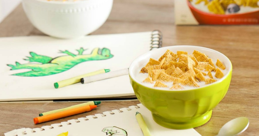 Life Cereal in a green bowl with milk near cereal box and drawing of a dinosaur
