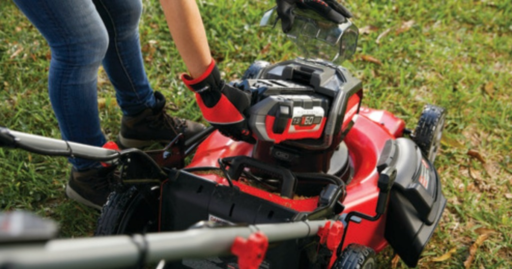 woman putting battery in Craftsman mower