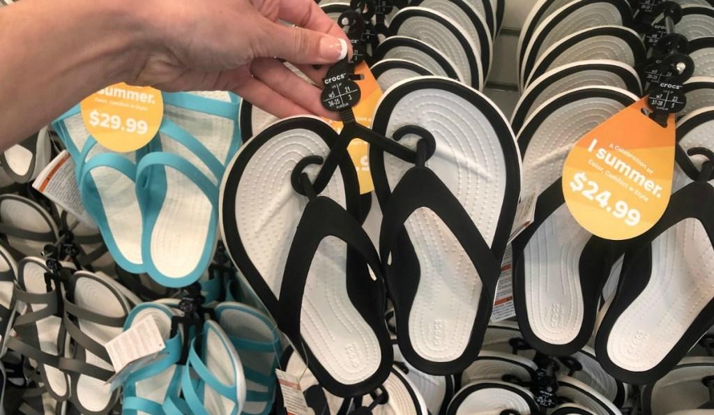 Crocs Flip Flops in black and white in hand on hanger in store