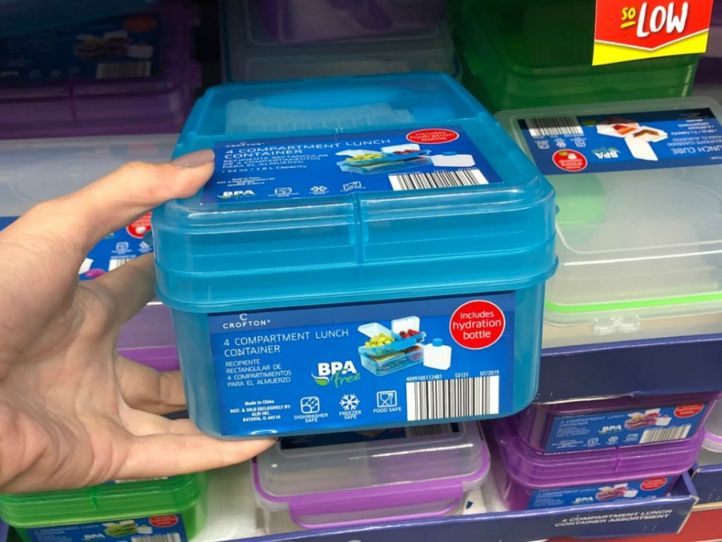 hand holding plastic lunch box by store display