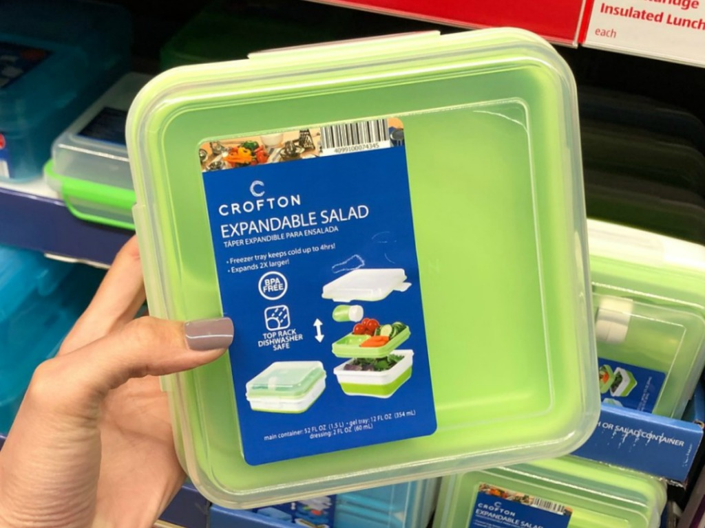 hand holding green container for lunches by store display