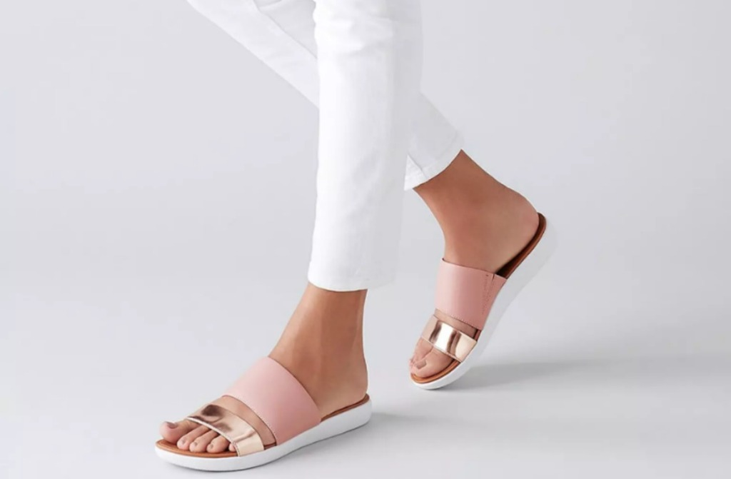woman in white pants wearing pink and gold slides