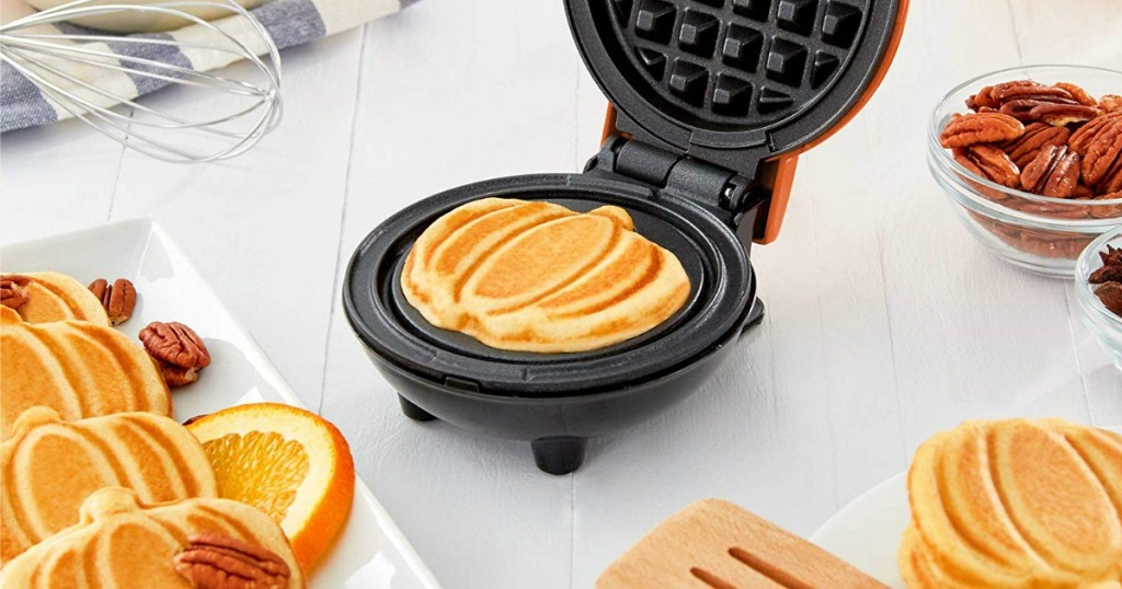 Dash Mini Pumpkin Waffle Maker on kitchen counter with pumpkin shaped waffles