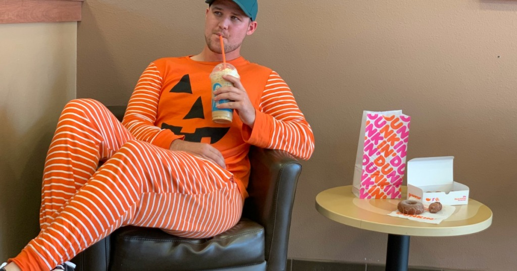 Man in Pumpkin costume trying Dunkin Fall items