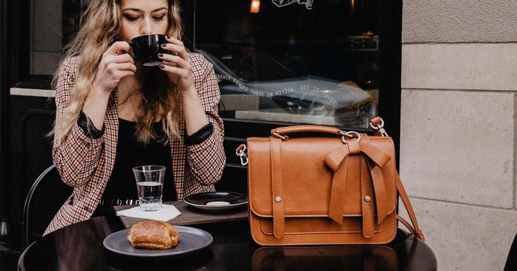 woman drinking coffee at table with ECOSUSI Women's Small Vintage Vegan Leather Crossbody Satchel Bag with Detachable Bow