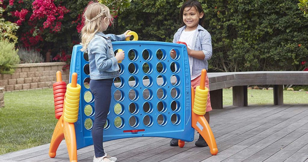 two kids playing with ECR4Kids Junior 4-to-Score Giant Game Set on backyard patio