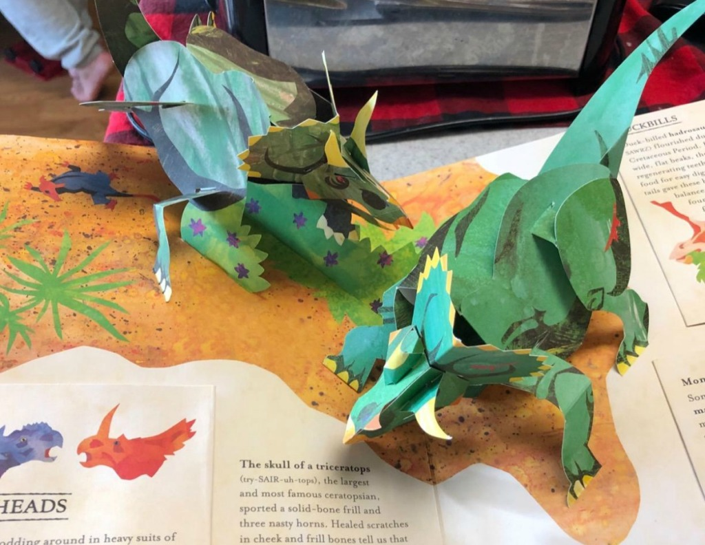 green dinosaurs in pop-up book