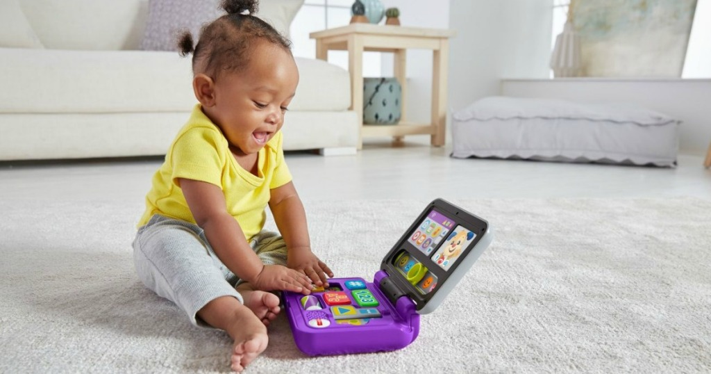 baby girl playing with Fisher-Price toy laptop