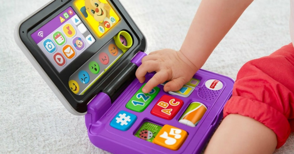 closeup of child playing with a Fisher-Price toy laptop